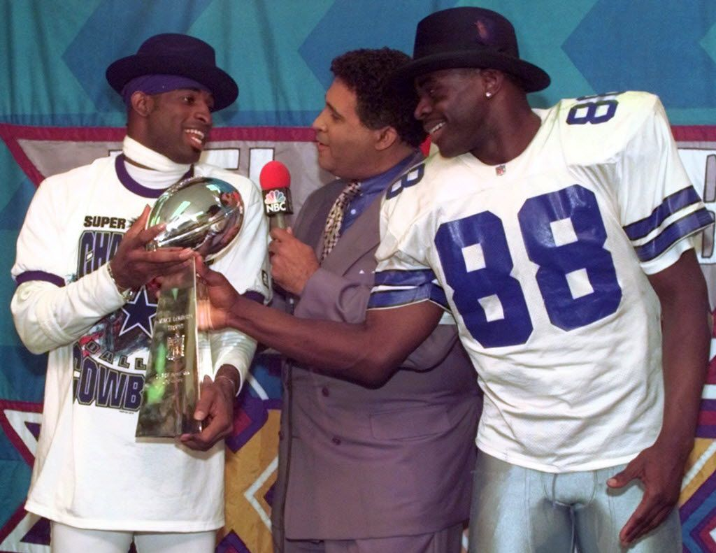 Dallas Cowboys cornerback Deion Sanders, left, and running back Michael Irvin (88) share the Vince Lombardi trophy as NBC commentator Greg Gumbel interviews the two after Super Bowl XXX in Tempe, Ariz., Sunday, Jan. 28, 1996.  The Cowboys beat the Pittsburgh Steelers 27-17. (AP Photo/Ron Heflin) ORG XMIT: PNX226