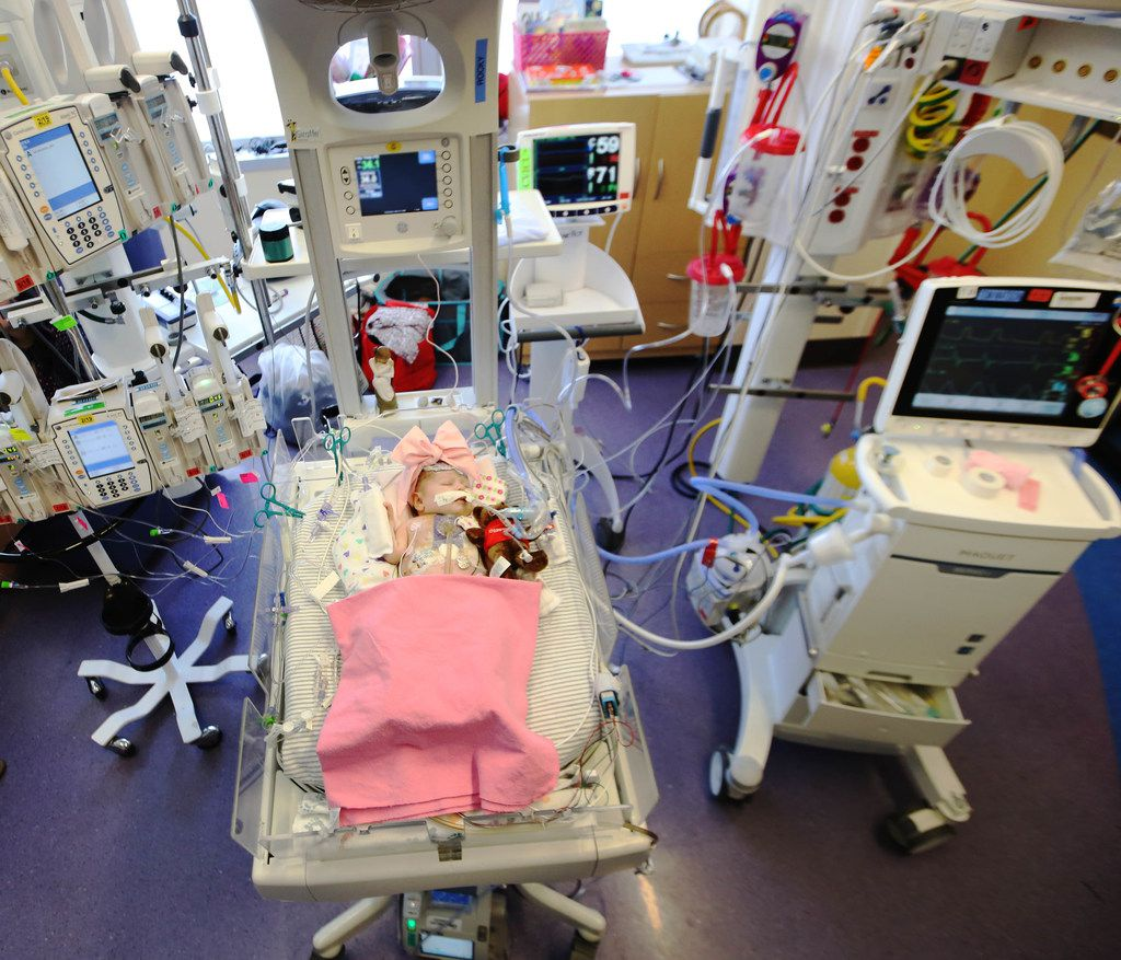 Olivia lies surrounded by the technology that has helped her cling to life. Faith has helped her parents stay strong.
