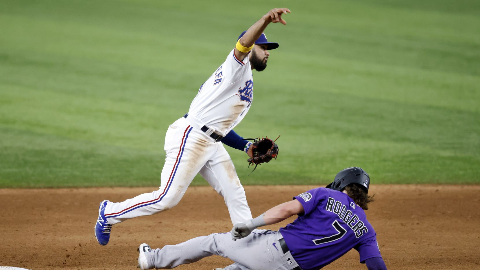 Texas Ranger shortstop Isiah Kiner-Falefa (9) turns the front end of an attempted double play getting Colorado Rockies Brendan Rodgers (7) during the fifth inning at Globe Life Park in Arlington, Texas Wednesday, September 1, 2021. The throw to first was late.