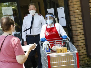 Salvation Army Major Todd Hawks, back, assists employee Maria Rincon, center, with a food pickup at The Salvation Army Oak Cliff on Thursday, July 9, 2020 in Dallas.