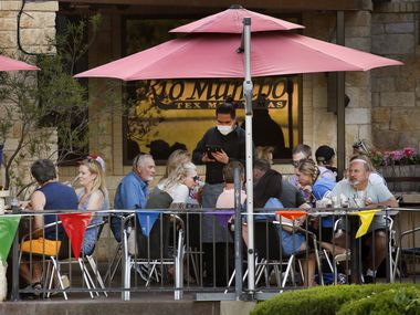 On April 24, the first day of outdoor patios being reopened, a waiter wearing a face mask takes orders from diners at Rio Mambo Tex Mex in Colleyville.