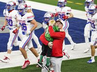 Austin Westlake head coach Todd Dodge hugs his grandson Tate, 5, as his team takes the field to warm warm up before facing his son, Southlake Carroll head coach Riley Dodge, in the Class 6A Division I state football championship game at AT&T Stadium on Saturday, Jan. 16, 2021, in Arlington, Texas. (Smiley N. Pool/The Dallas Morning News)