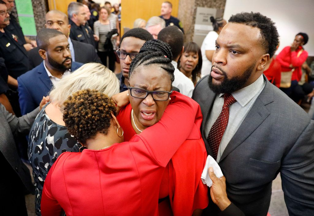 "Botham Jean's mother, Allison Jean (center) is hugged by family members outside the 204th District Court after fired Dallas police Officer Amber Guyger was found guilty of murder by a 12-person jury at the Frank Crowley Courts Building in Dallas, Tuesday, October 1, 2019. She was escorted by civil rights attorney Lee Merritt (right). She repeatedly said, ""God is good. Trust him,"" as she left the courtroom. Guyger shot and killed Botham Jean, an unarmed 26-year-old neighbor in his own apartment last year. She told police she thought his apartment was her own and that he was an intruder."