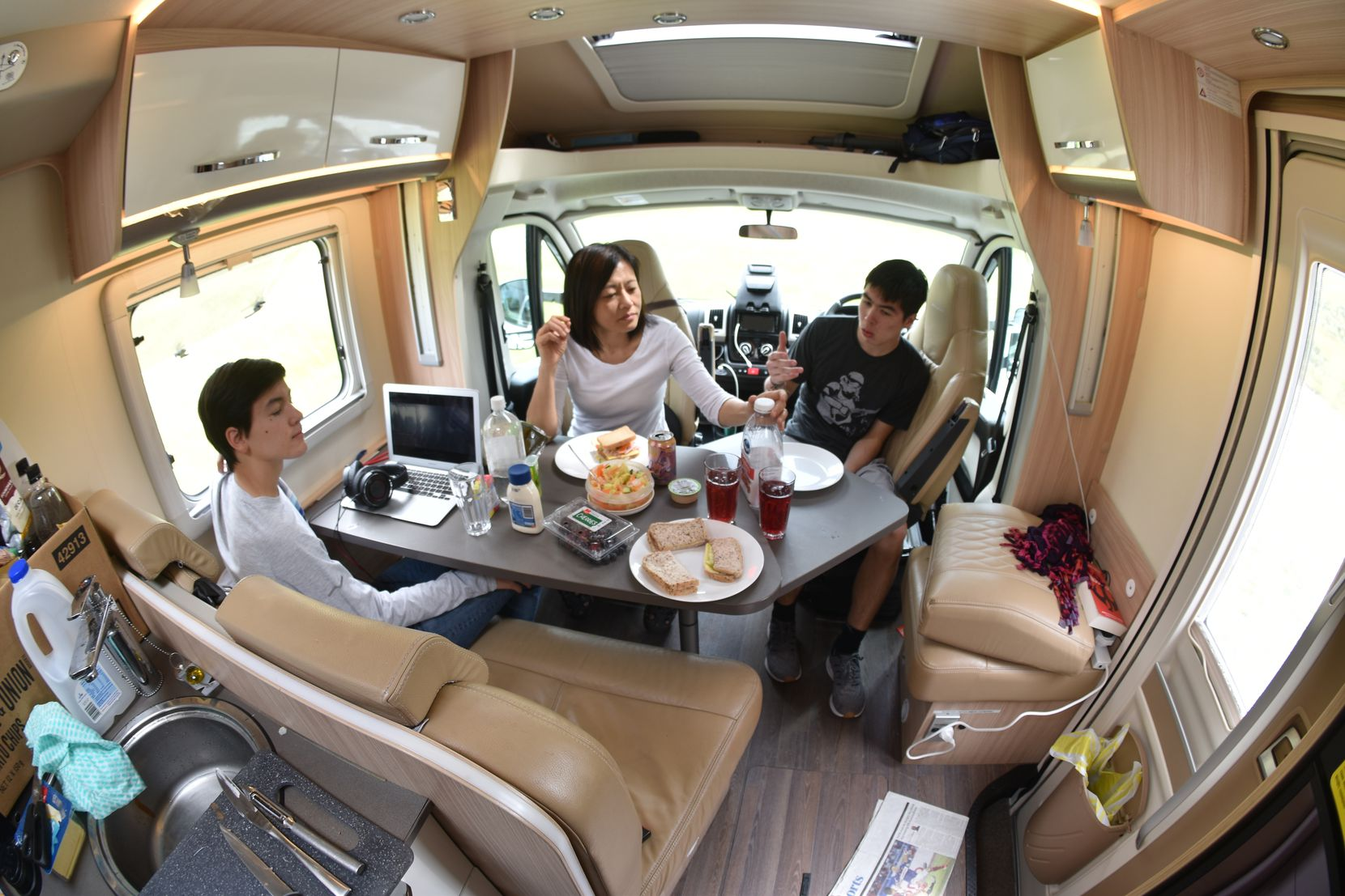 This photo taken using a fisheye lens shows the Foster family eating lunch in their rented camper van at a roadside stop on the South Island of New Zealand. Touring in a camper van is a popular way for tourists to see the country.