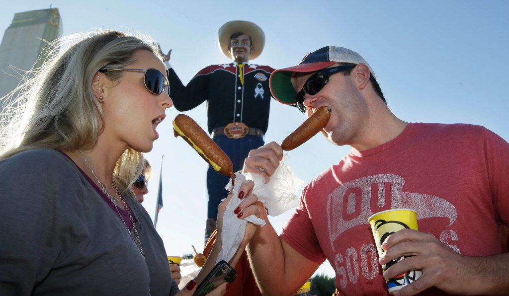 Gwin Huey, left, and her husband Ryan Huey eat corn dogs in front of Big Tex at the state fair before an NCAA college football game between Texas and Oklahoma in Dallas Saturday, Oct. 8, 2016. (AP Photo/LM Otero)
