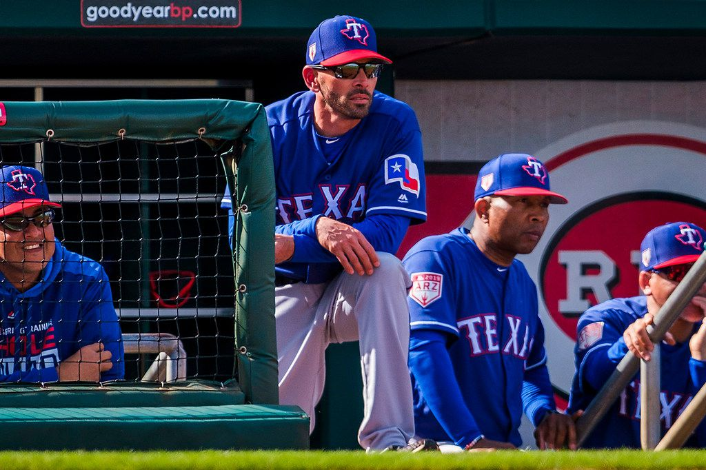 Texas Rangers manager Chris Woodward (center) watches from the top step of the dugout with (from left) pitching coach Julio Rangel, third base coach Tony Beasley and first base coach HŽctor Ortiz during a spring training baseball game against the Cleveland Indians on Monday, Feb. 25, 2019, in Goodyear, Ariz.. (Smiley N. Pool/The Dallas Morning News)