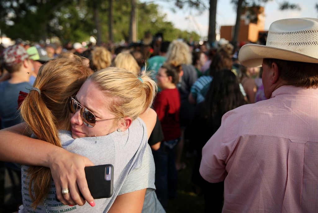 Mourners embrace during a vigil following a shooting at Santa Fe High School on May 18.