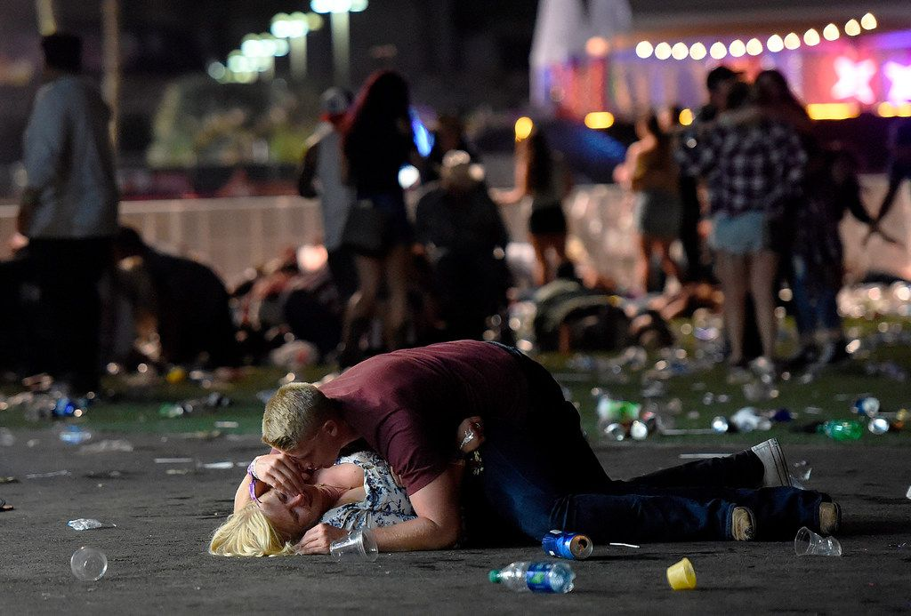 A man lays on top of a woman as others flee the Route 91 Harvest country music festival grounds during a shooting rampage in Las Vegas on Oct. 1, 2017.