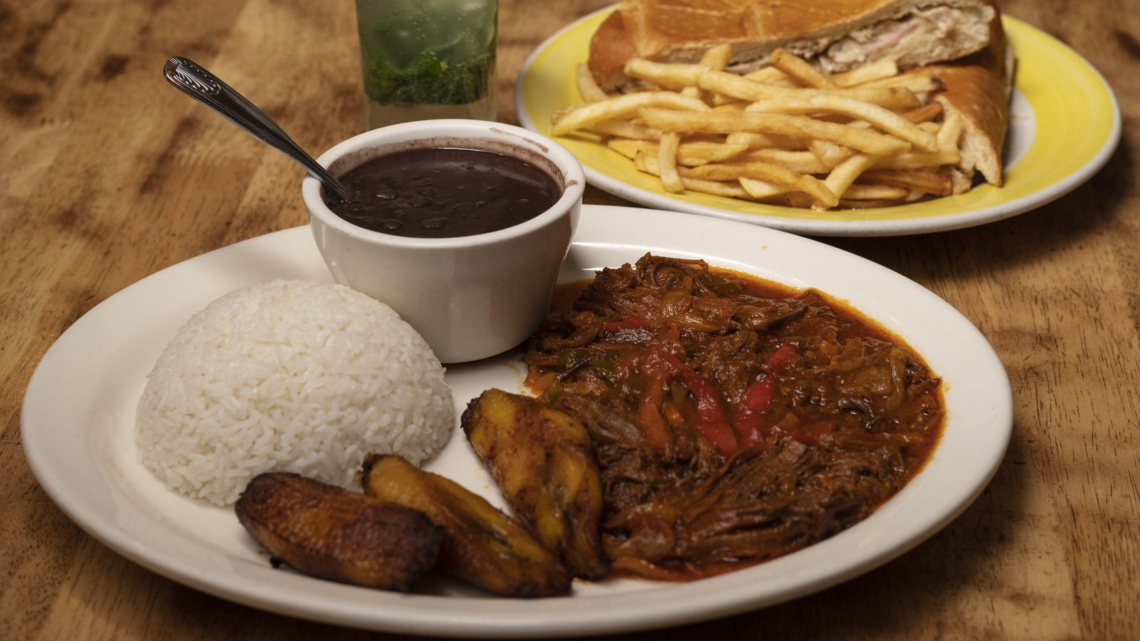A dish of Ropa Vieja, shredded beef in a tomato sauce, with red, green peppers and onion, center, and a Cuban sandwich with sliced pork, ham and Swiss cheese, served with fries, from Caribbean Cuba restaurant in Carrollton