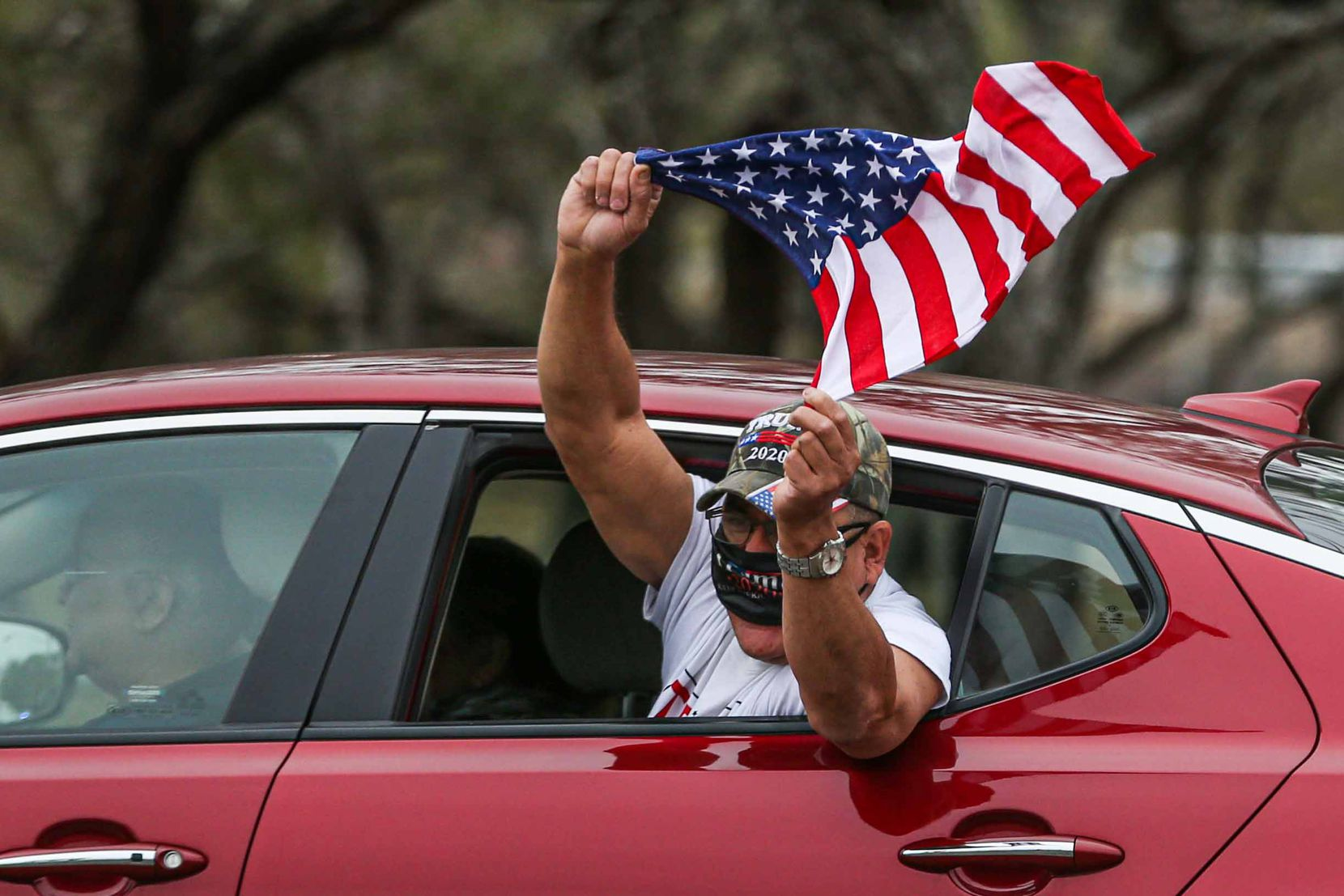A man shouts from a car window in motion holding an American flag as he passes in front of a rally in support of President Donald Trump that is scheduled to visit part of the wall built under his mandate in McAllen on Tuesday, January 12, 2021.