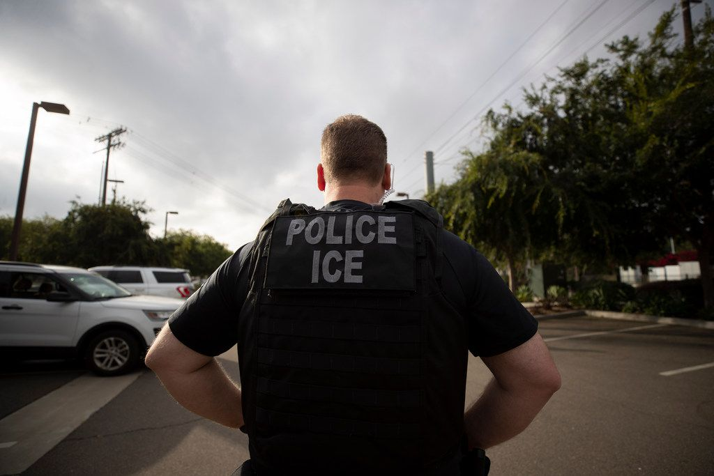 A U.S. Immigration and Customs Enforcement officer looks on during an operation in Escondido, Calif on July 8, 2019. The carefully orchestrated arrest last week in this San Diego suburb illustrates how President Donald Trump's pledge to start deporting millions of people in the country illegally is virtually impossible with ICE's budget and its method of picking people up.