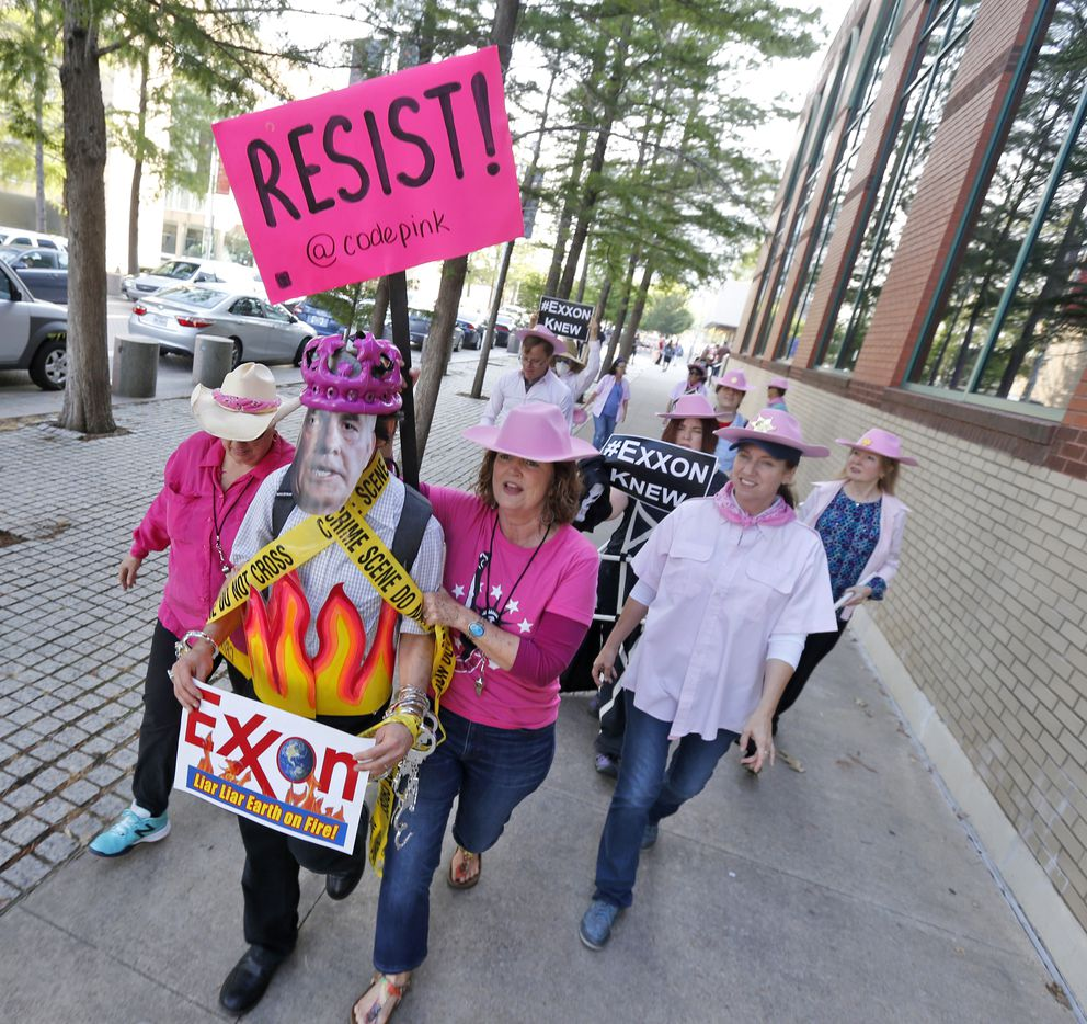 Members of Code Pink, led by Danna Miller Pyke (front with sign), picket and stage a mock arrest of Rex Tillerson, worn by Ernest Jones, as protesters gather outside of the Exxon shareholders meeting across the street from Morton H. Meyerson Symphony Center in Dallas on May 31, 2017.  (Nathan Hunsinger/The Dallas Morning News)