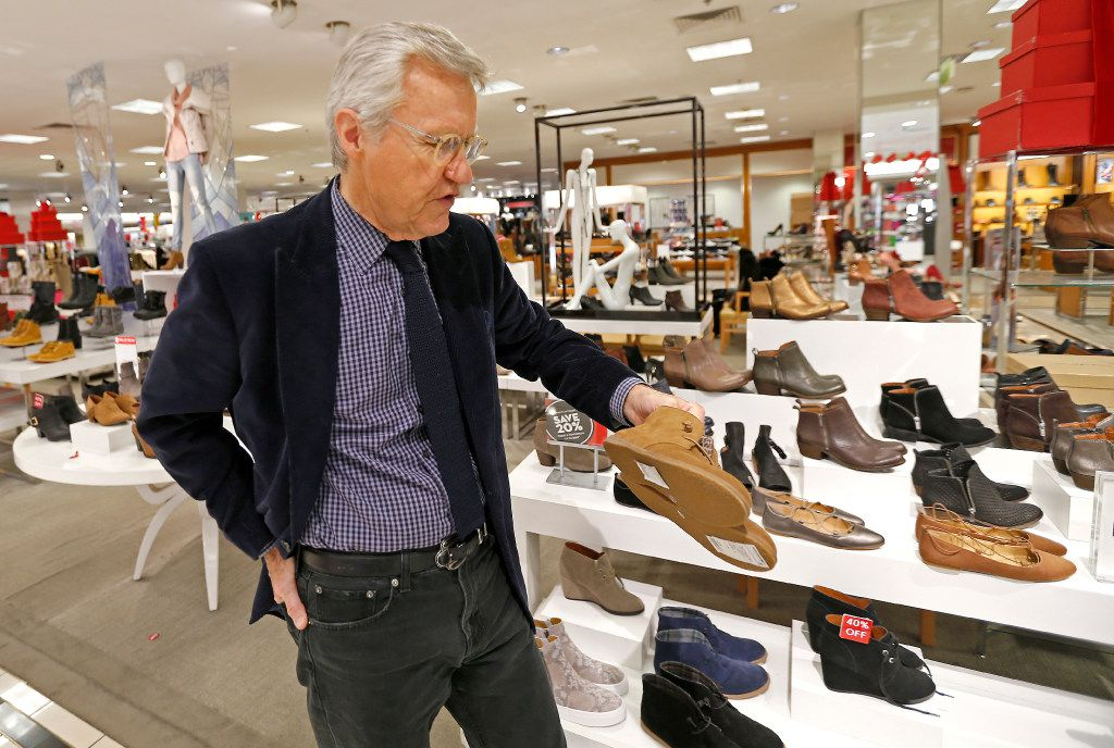 Allen Questrom talks about a pair of women's shoes while touring at the Macy's department store in 2016 at NorthPark Center in Dallas.