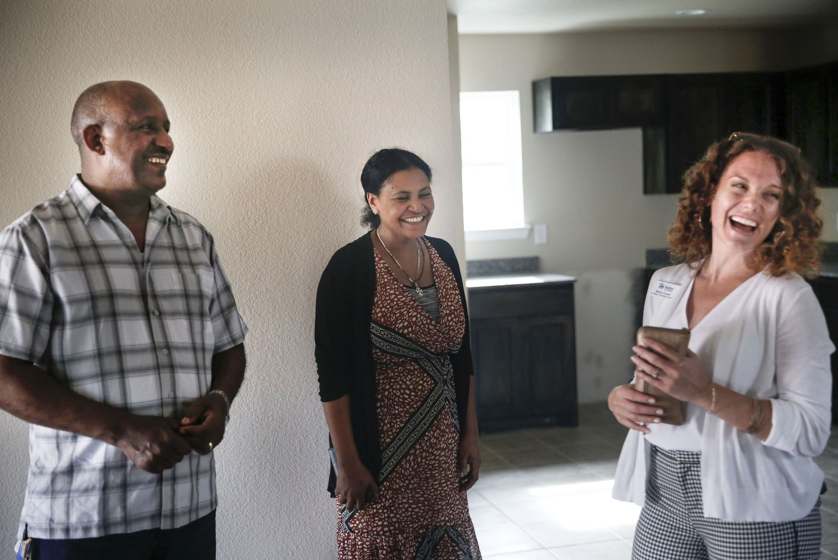 New homeowners Terefe Bezabeh (left) and Tequadesh Eshibelachew (center) walk through their new Habitat for Humanity home in West Dallas with Habitat for Humanity Senior Director of Home Owner Services Blaine Cowart.