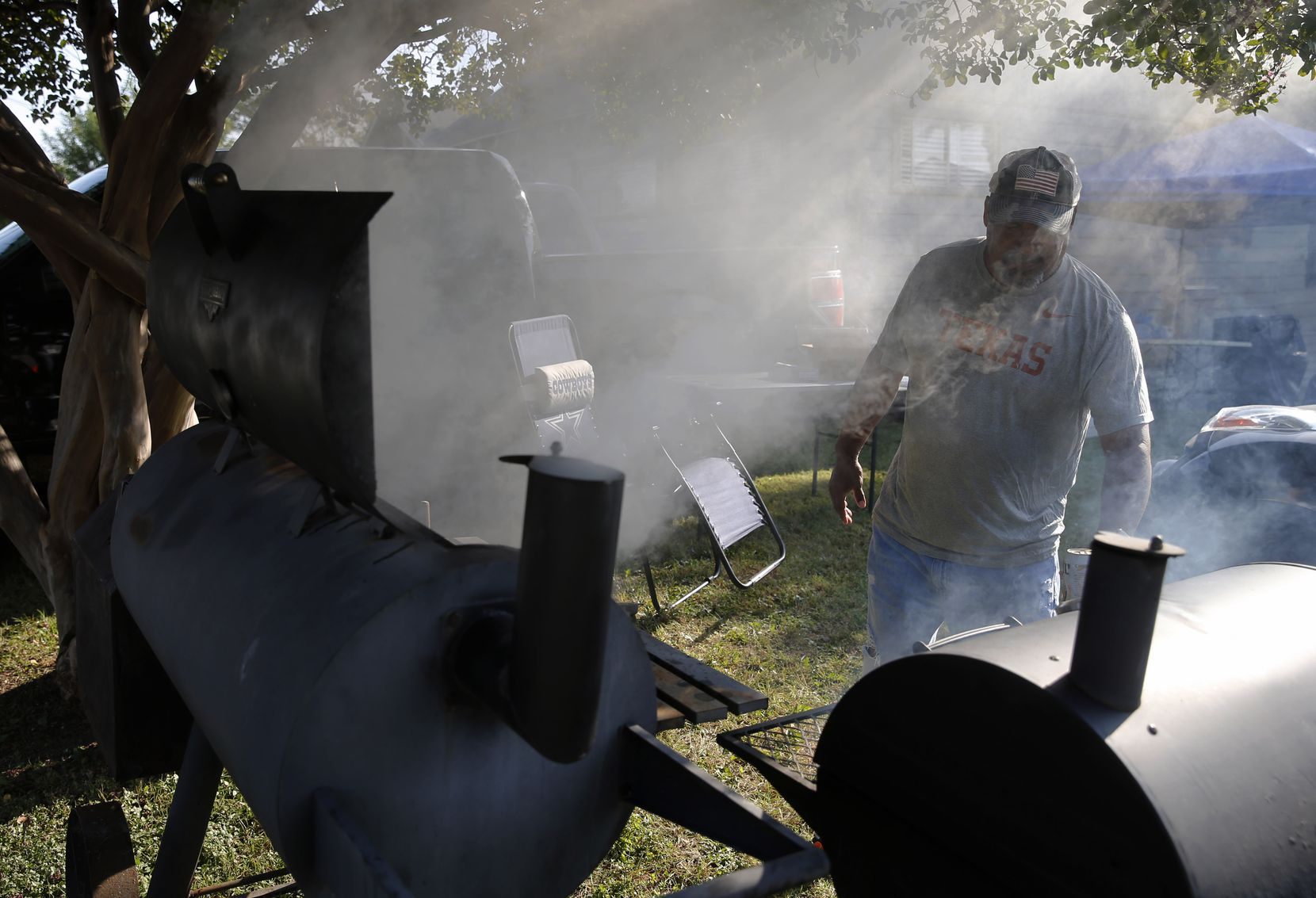 Stacey Walker of Dallas tends to the pit at a friend's house near Fair Park on Saturday, Oct. 10, 2020. The Longhorns fan is cooking in preparation for the arrival of the Sooners fans he sees during the annual Texas vs. Oklahoma football matchup. The group has met up for over a decade.