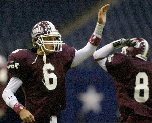Ennis quarterback Graham Harrell celebrates with teammate Brad Cepak (81) in the second half of their playoff game at Texas Stadium November 21, 2003.