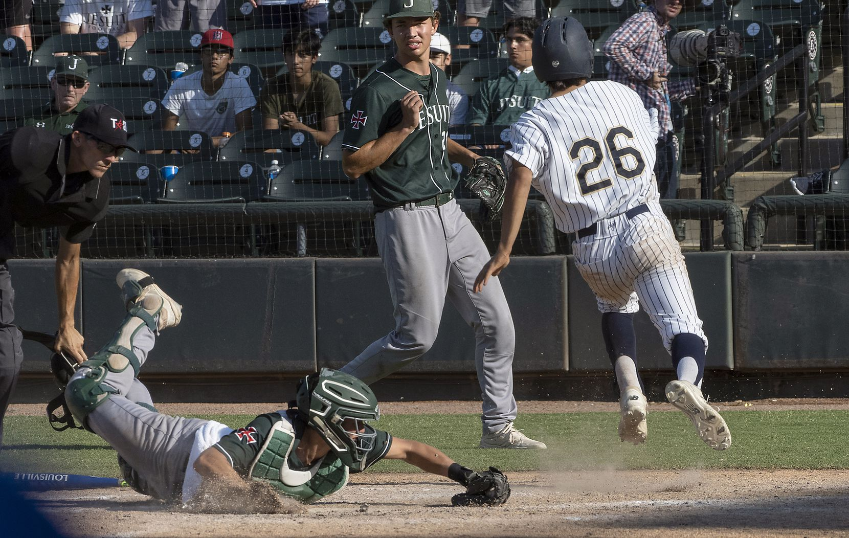 Keller Colten Vargas, (26), beats the tag at home plate by Houston Strake Jesuit catcher, James Vaquero, (15), as Carson Brown, (23), looks on during the fifth inning of the 2021 UIL 6A state baseball semifinals held, Friday, June 11, 2021, in Round Rock, Texas.     Keller defeated Strake Jesuit 7-1. (Rodolfo Gonzalez/Special Contributor)