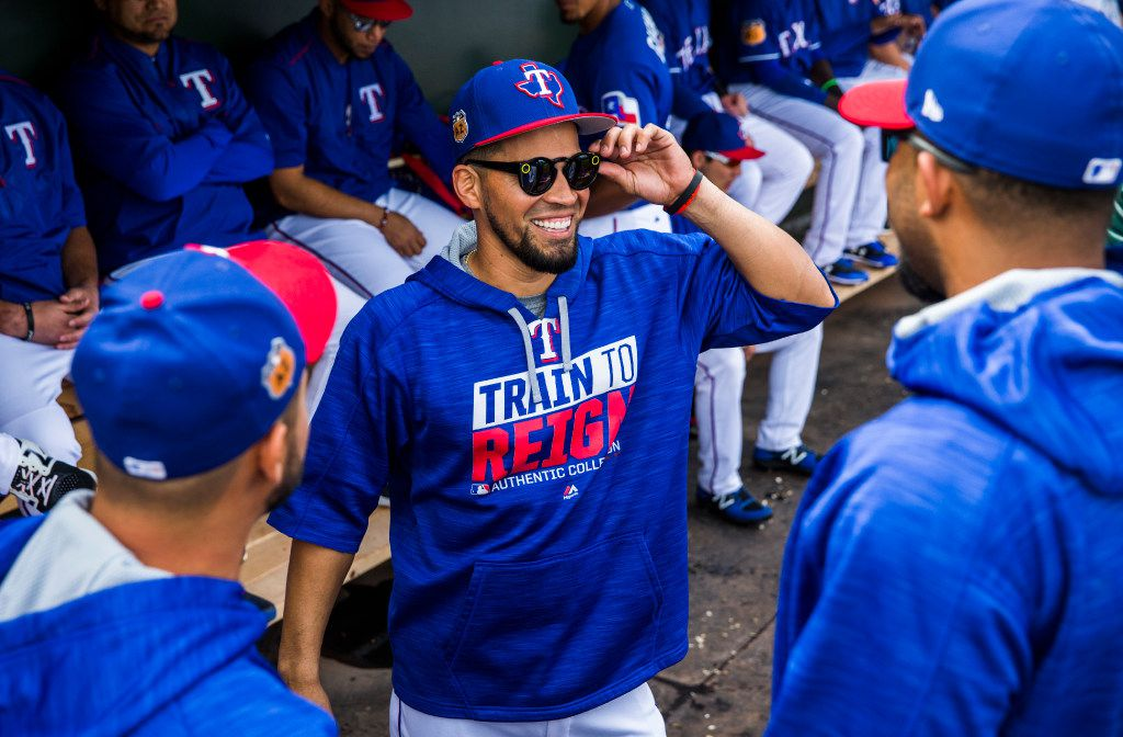 Texas Rangers catcher Robinson Chirinos (61, center) shows off his shades to starting pitcher Martin Perez (33) and shortstop Elvis Andrus (1) in the dugout before a spring training baseball game against the Seattle Mariners at their training facility on Friday, March 3, 2017 in Surprise, Arizona. (Ashley Landis/The Dallas Morning News)