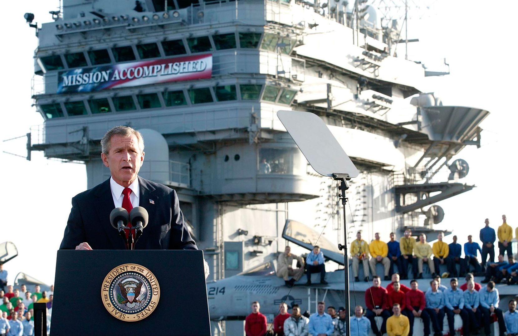 """President George W. Bush addresses the nation on May 1, 2003, from the nuclear aircraft carrier USS Abraham Lincoln as it sails for San Diego, Calif. A banner proclaiming """"Mission Accomplished"""" loomed in the background as he declared the end of major combat operations in Iraq, a claim belied by the years of hard fighting that followed."""