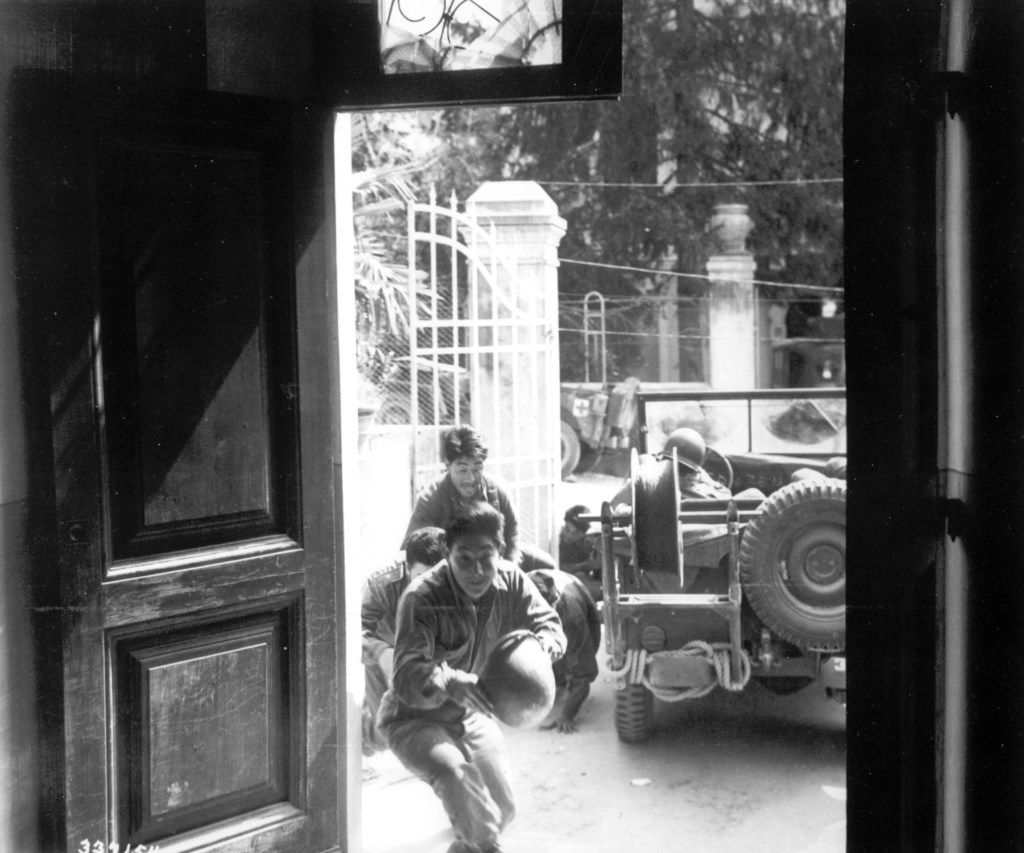 Japanese American infantrymen of the 442nd regiment are running for cover inside a building as they are targeted by German artillery in an unknown Italian town, on April 4, 1945.