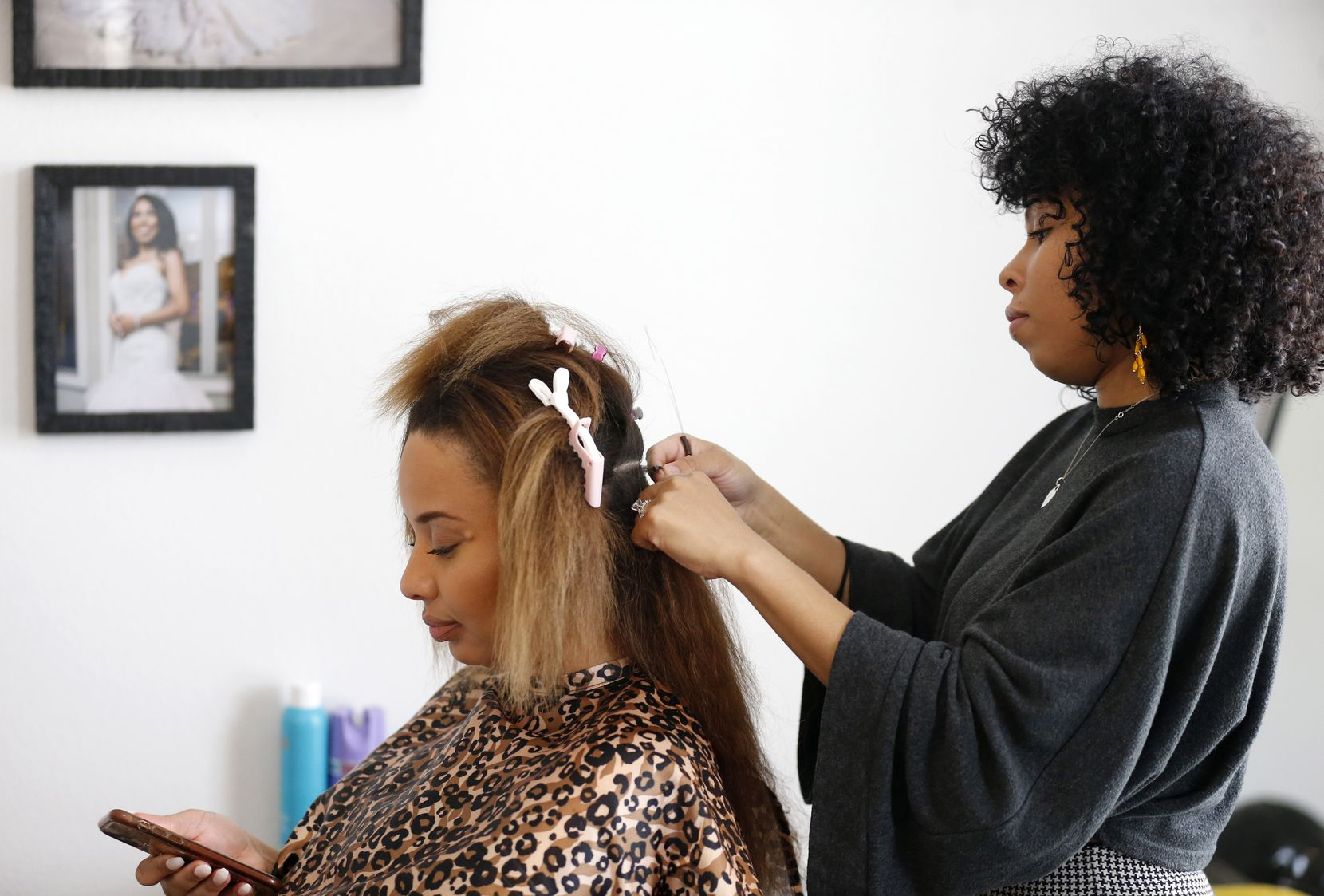 Monique Campbell works on her friend Kierra Walker's hair at her home in Melissa, Texas.