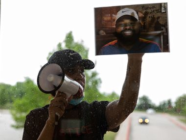 Renee White presses a photo of Marvin Scott III on the windows of the Collin County Courthouse while demanding the officers present arrest the officers involved in Scott's in-custody death after a press conference on April 28, 2021.