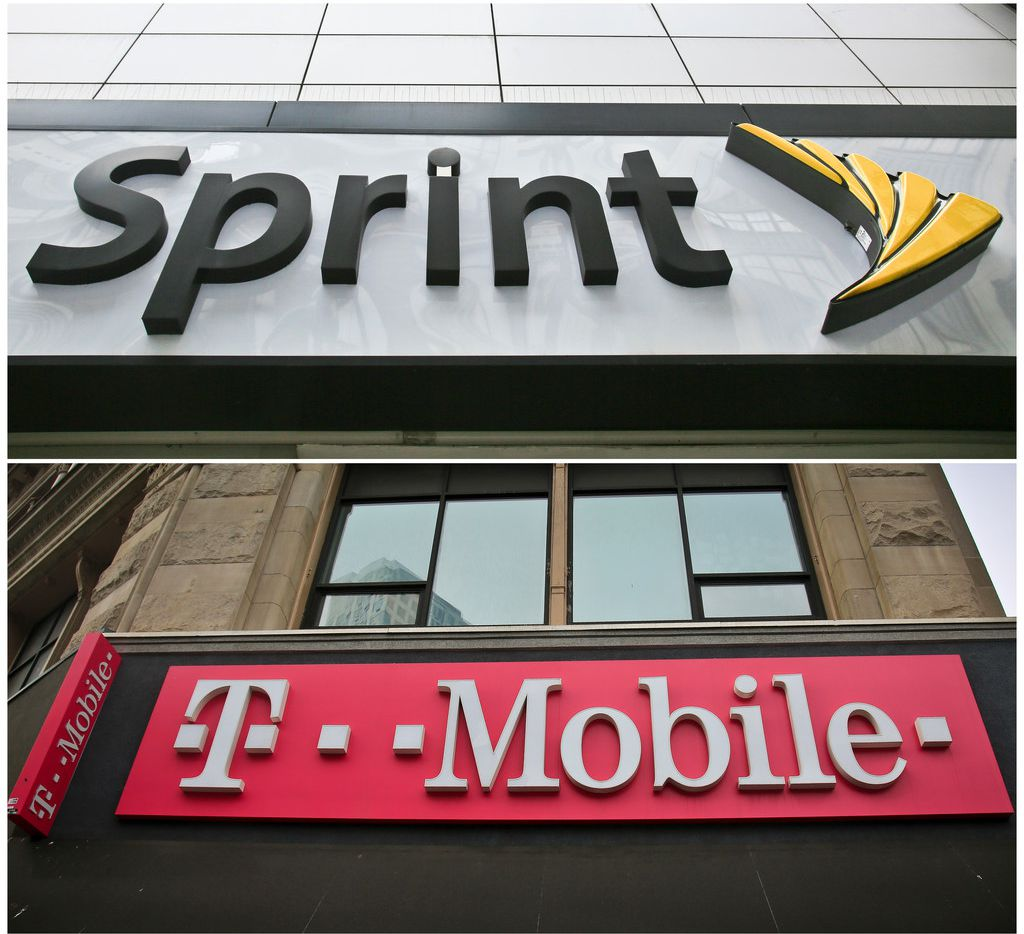 This combination of file photos shows signage for a Sprint store in New York's Herald Square, top, and signage at a T-Mobile store in New York.