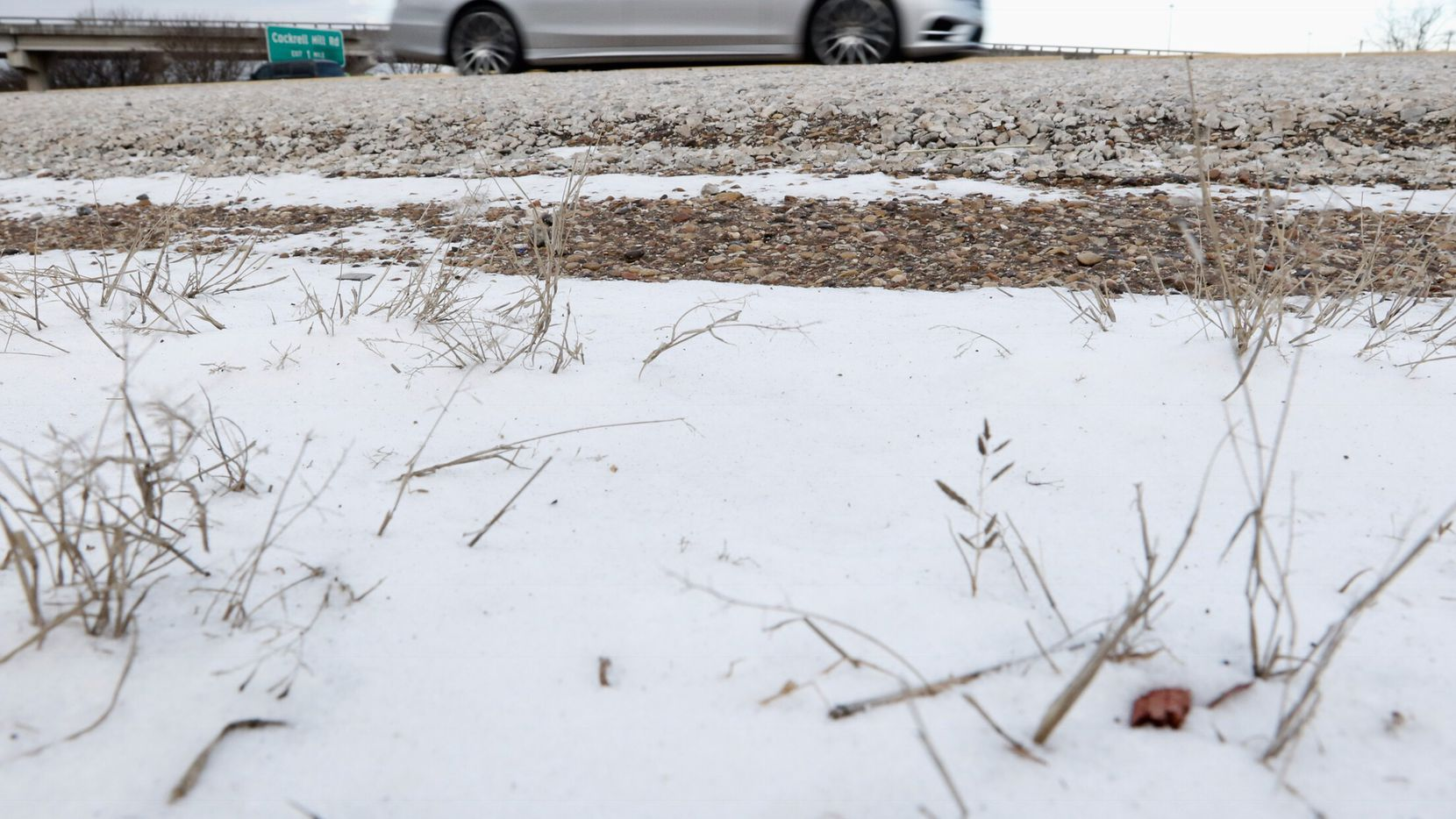 A car passed wind-blown snow last year along U.S. Highway 67 and Interstate 20 in southern Dallas.