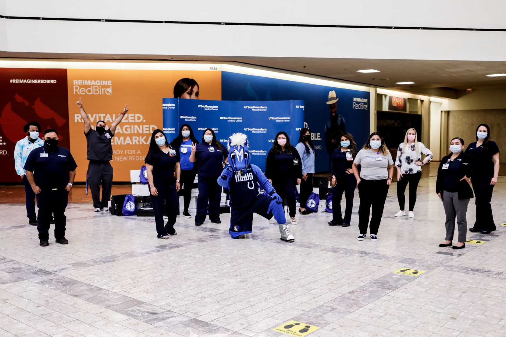 Dallas Mavericks mascot Champ, poses with UT Southwestern healthcare workers after they received a donation of 100 pairs of Air Jordan 1s from Mavs' star Luka Doncic.