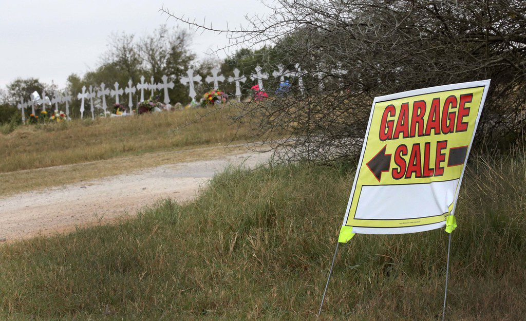 A sign for a garage sale stands outside the Ward residence on 13th Street in Sutherland Springs, near where 26 crosses honor those who died Sunday when gunman opened fire at a Baptist church in the town. The Ward family lost three members in the shooting and another is recovering from multiple gunshot wounds.