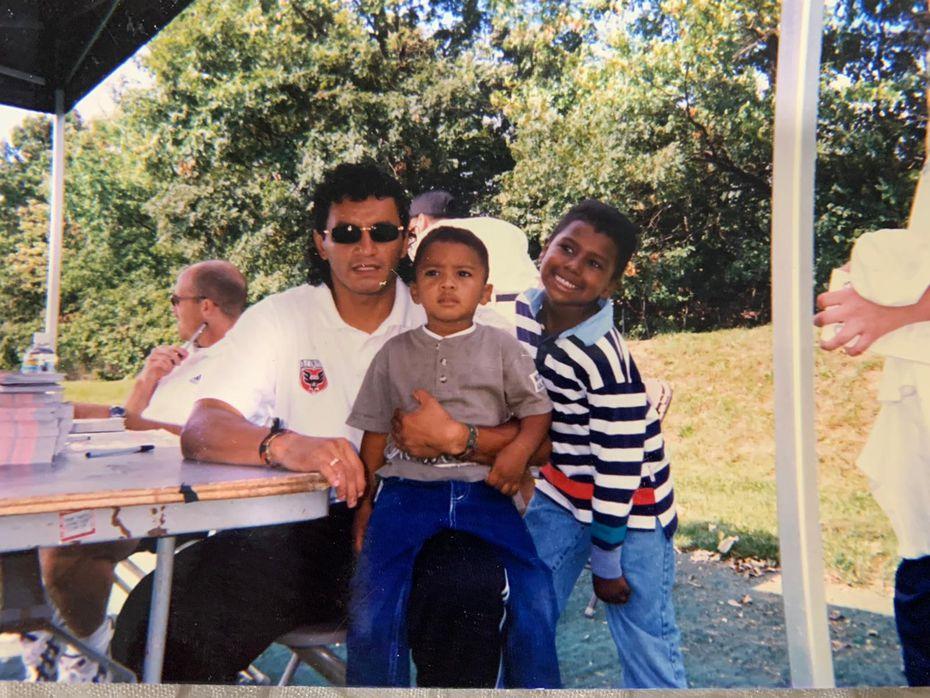 """En esta fotografía tomada en  el año 2000, se ve al legendario futbolista de Bolivia, Marco Antonio """"El Diablo"""" Etcheverry, cargar en sus piernas a Josh Reaves, y al lado se ve Michael, hermano mayor de Josh."""