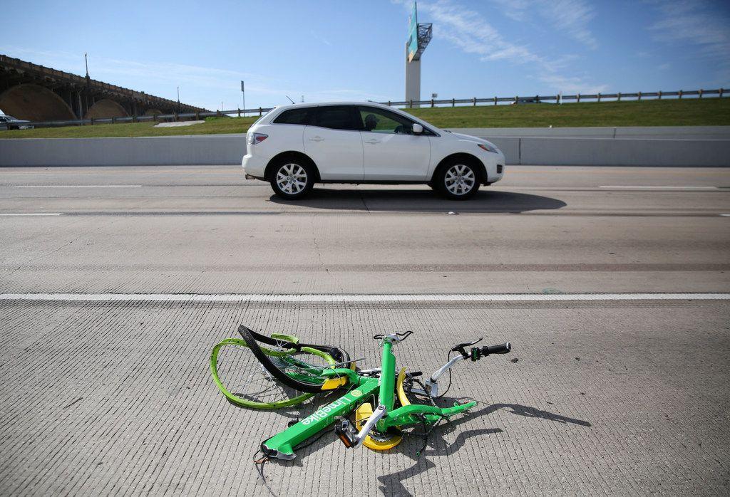 The mangled remains of a LimeBike rental bike lie alongside I-35E in downtown Dallas on Nov. 11, 2017.