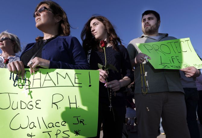 Rosie, Mary Kate and Thomas Levitt protested with a group in front of John Peter Smith Hospital after a pregnant, brain-dead woman was removed from life support in Fort Worth on Sunday.
