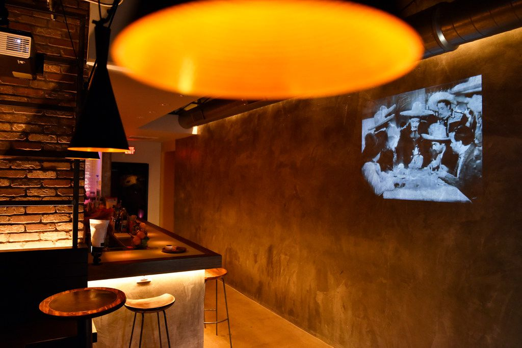 A projector plays old black-and-white Mexican TV shows on a wall at La Viuda Negra, a new speakeasy-style bar in Dallas.