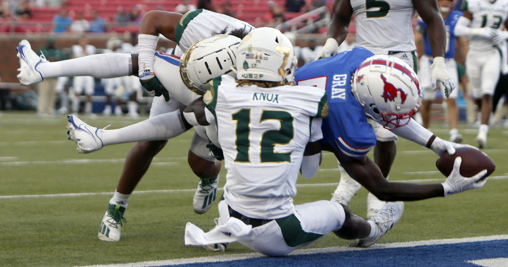 SMU receiver Danny Gray (5) dives into the end zone despite the defensive efforts of South Florida cornerback Ben Knox (12) and safety Matthew Hill (1) following a 4th quarter reception. SMU defeated South Florida 41-17. The two teams played their NCAA football game at SMU's Ford Stadium in Dallas on October 2, 2021. (Steve Hamm/ Special Contributor)