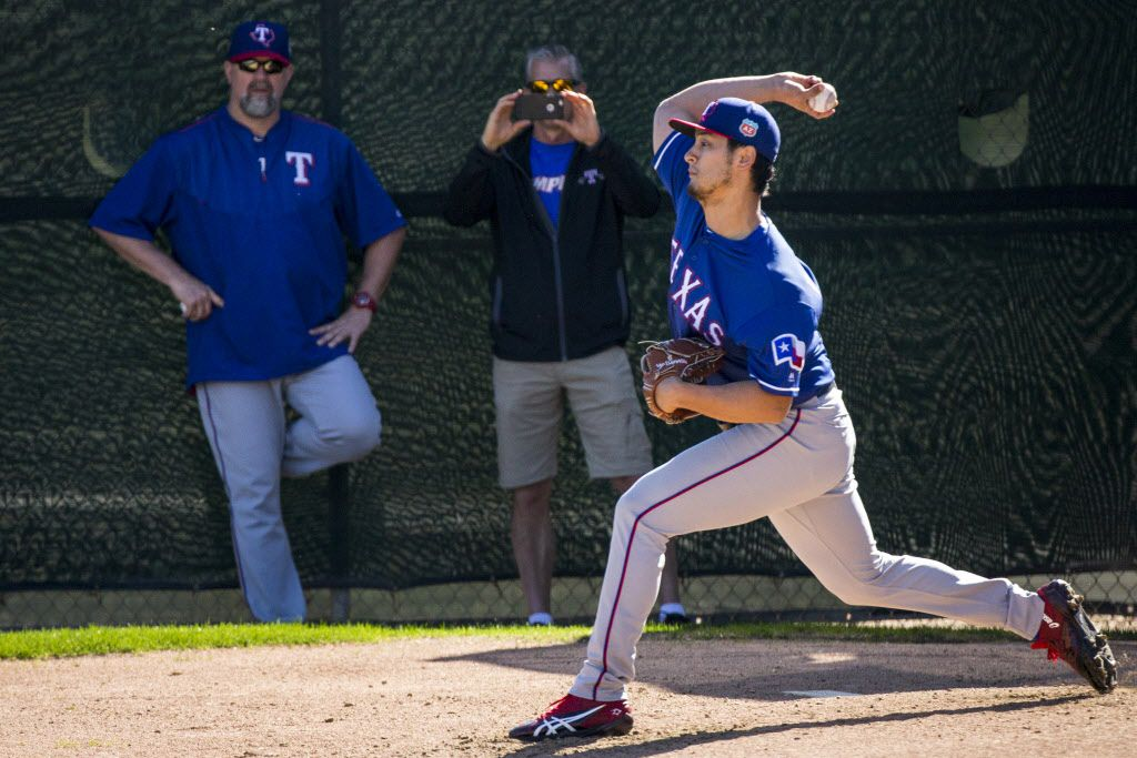 Texas Rangers pitcher Yu Darvish throws from a half pitching mound under eye of Rangers pitching coach Doug Brocail (left) during a spring training workout at the team's training facility on Monday, Feb. 22, 2016, in Surprise, Ariz. (Smiley N. Pool/The Dallas Morning News)