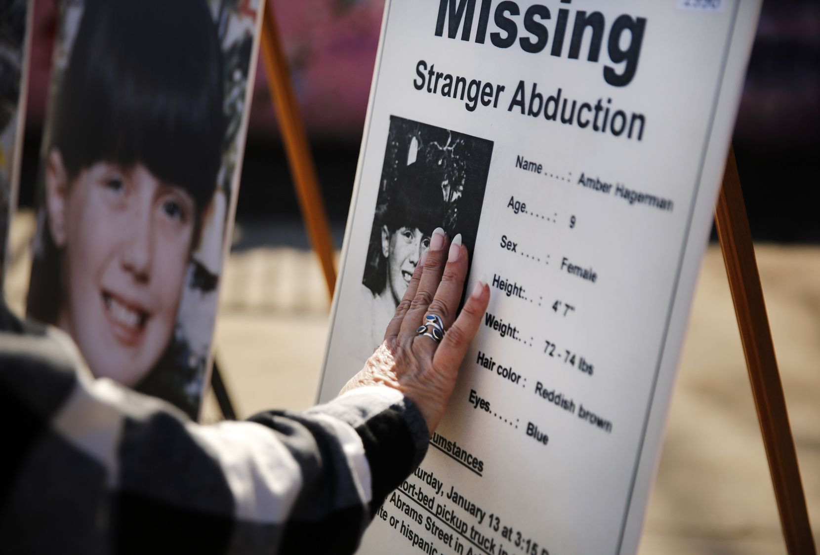 Amber Hagerman's mother Donna Williams touches a photo of her daughter on the original 'Missing' poster that was displayed during a press conference at the abduction site in E. Arlington, Texas, Wednesday, January 13, 2021.