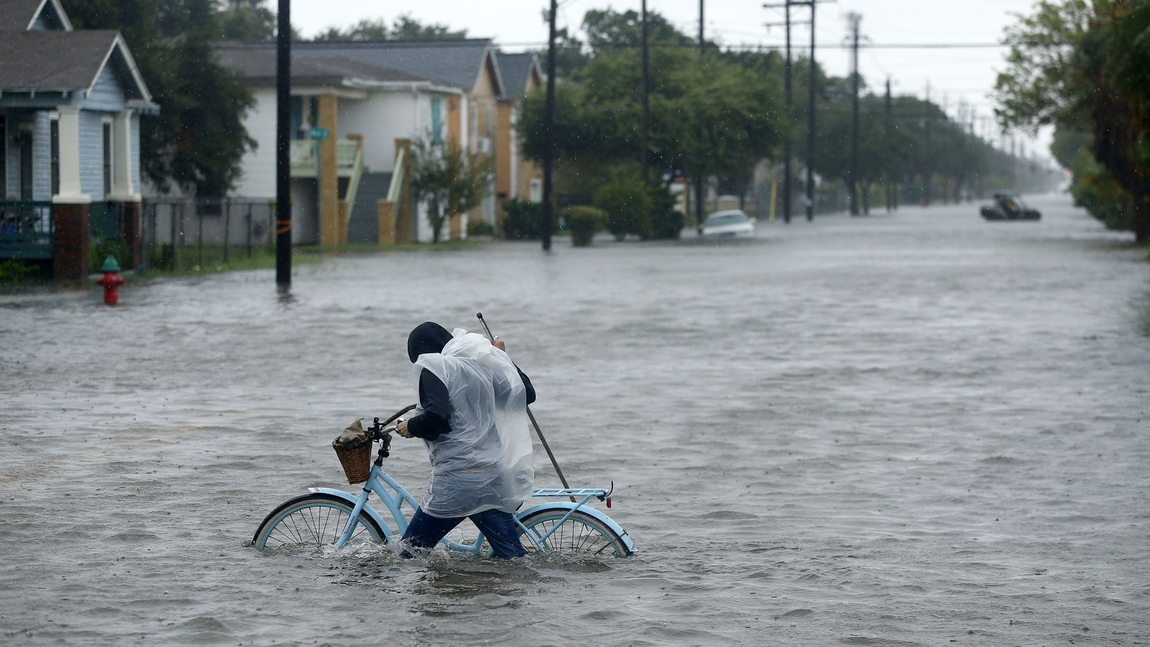 Monica Grant pushes her bike through flooded streets near Broadway Avenue in Galveston on Aug. 29 after Tropical Storm Harvey passed by the island.