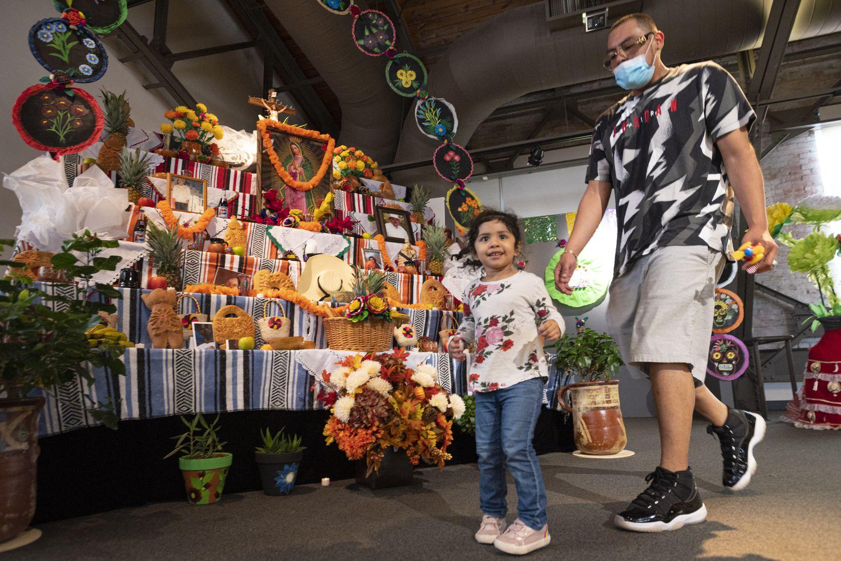 Sophia Rodríguez, de 3 años, y Alejandro Núñez recorren la exhibición del Día de los Muertos en Mundo Latino, una de las ofertas de la Feria Estatal en el Women's Building.