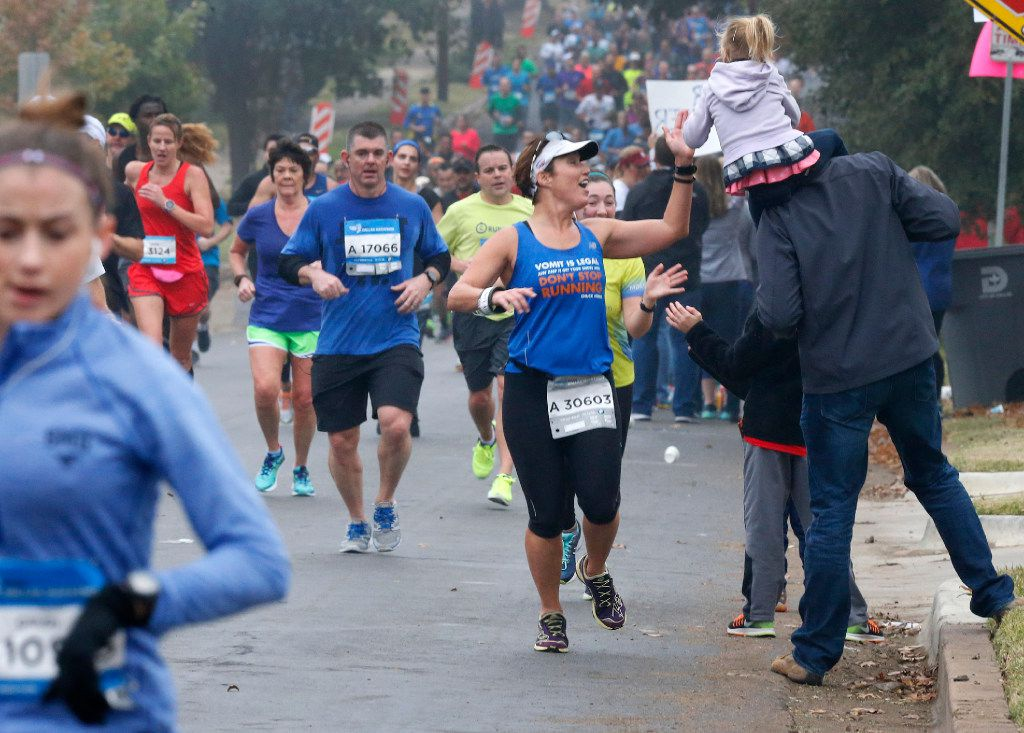 A runner high-fives a member of the crowd at the 8-mile mark of the 2016 BMW Dallas Marathon.
