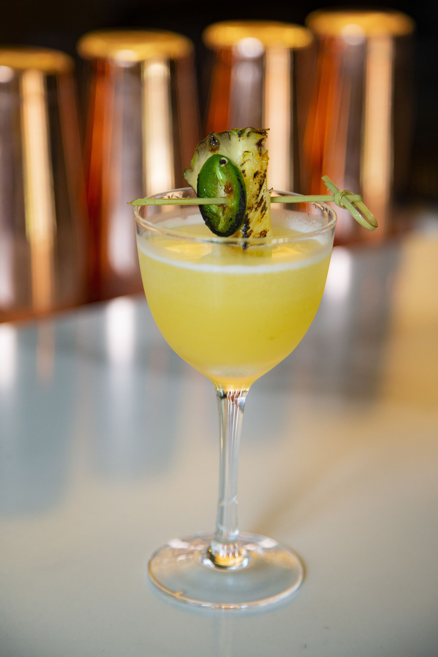 """An """"Alli Dee"""" cocktail, made primarily with tequila, pineapple and lime juice garnished with a torched pineapple slice and jalapeño at Side Saddle in the Fort Worth Stockyards."""