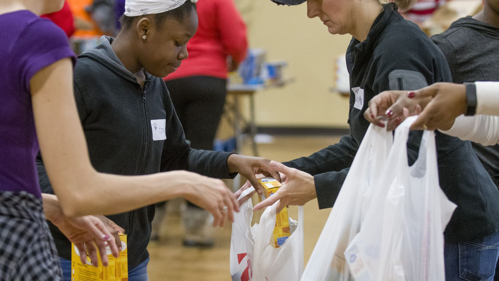 Volunteers at Youth World fill bags of groceries for 300 needy families who received food and Christmas presents during the annual giveaway.