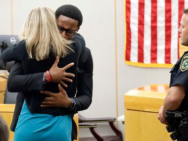 Brandt Jean hugs Amber Guyger in the courtroom Wednesday after saying he had forgiven her for killing his brother Botham.