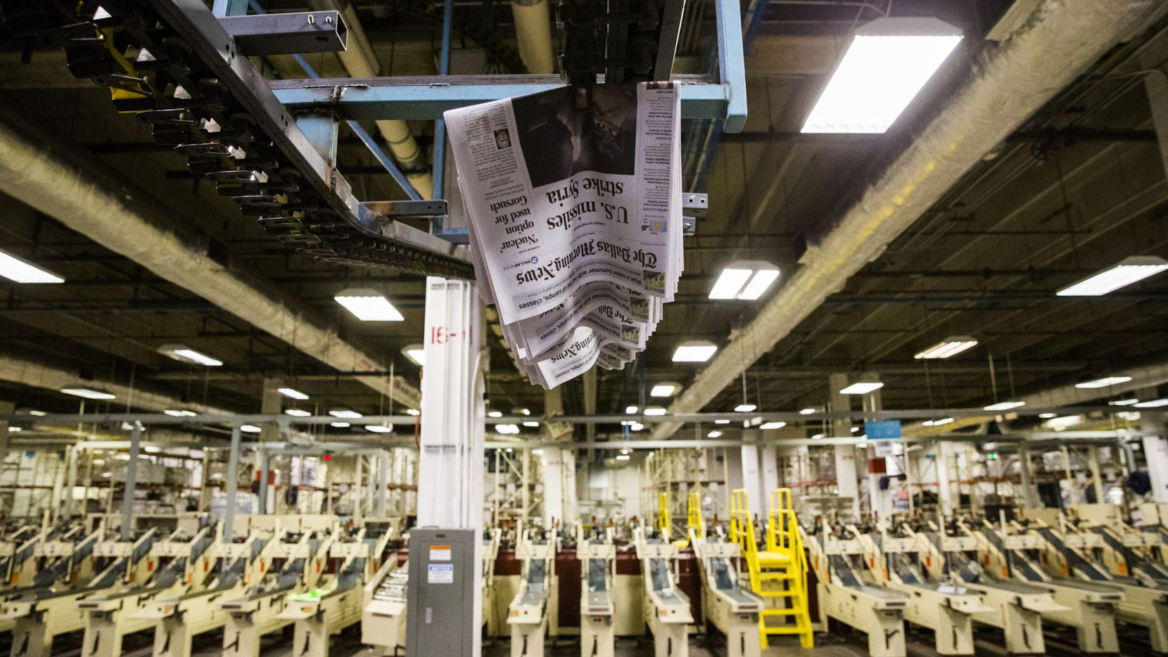 Copies of the Friday, April 7, 2017 issue of The Dallas Morning News newspapers move overhead on Thursday, April 6, 2017 at The Dallas Morning News' North Plant in Plano, Texas. (Ashley Landis/The Dallas Morning News)
