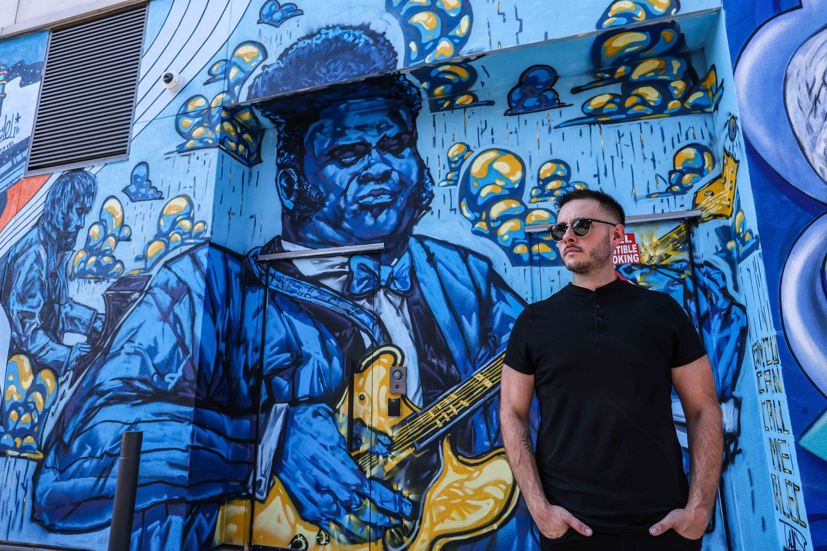 """Alec DeJesus poses by his contribution to the alley, """"The Texas Cannonball,"""" which shows Freddie King."""