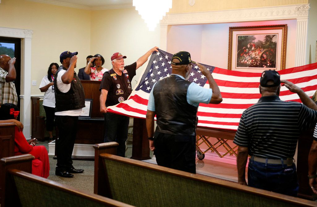 People salute as the Patriot Guard hold the American flag during a wake for Willie B. Ludden Jr. at Evergreen Memorial Funeral Home in Dallas on Tuesday