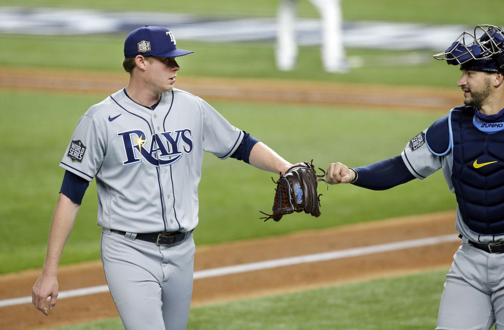 Tampa Bay Rays relief pitcher Peter Fairbanks (29) receives a fist bump from catcher Mike Zunino (10) after getting out of the seventh inning against the Los Angeles Dodgers in Game 2 of the World Series at Globe Life Field in Arlington, Wednesday, October 21, 2020. (Tom Fox/The Dallas Morning News)