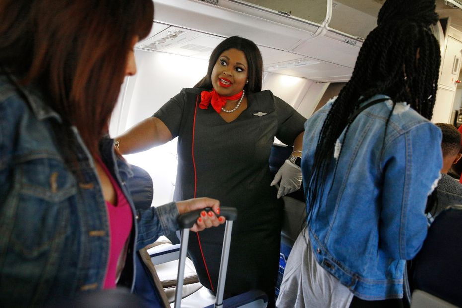 Southwest flight attendant Kelanie Watty, in her new uniform, talked to passengers Monday as they exited a flight at Dallas Love Field.