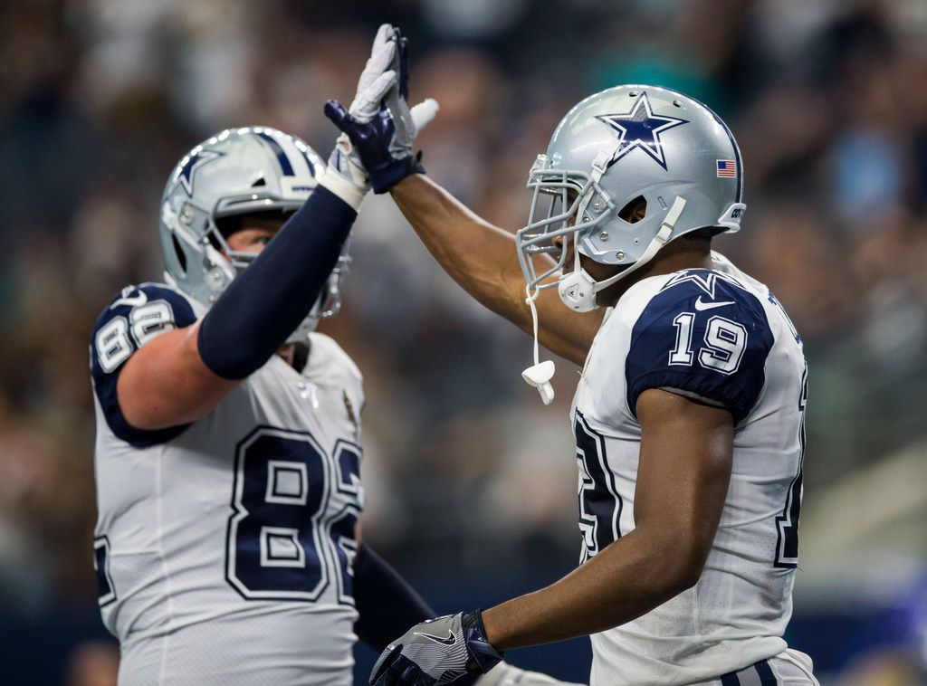 Dallas Cowboys wide receiver Amari Cooper (19) high-fives tight end Jason Witten (82) after scoring a touchdown during the third quarter of an NFL game between the Miami Dolphins and the Dallas Cowboys on Sunday, September 22, 2019 at AT&T Stadium in Arlington, Texas.