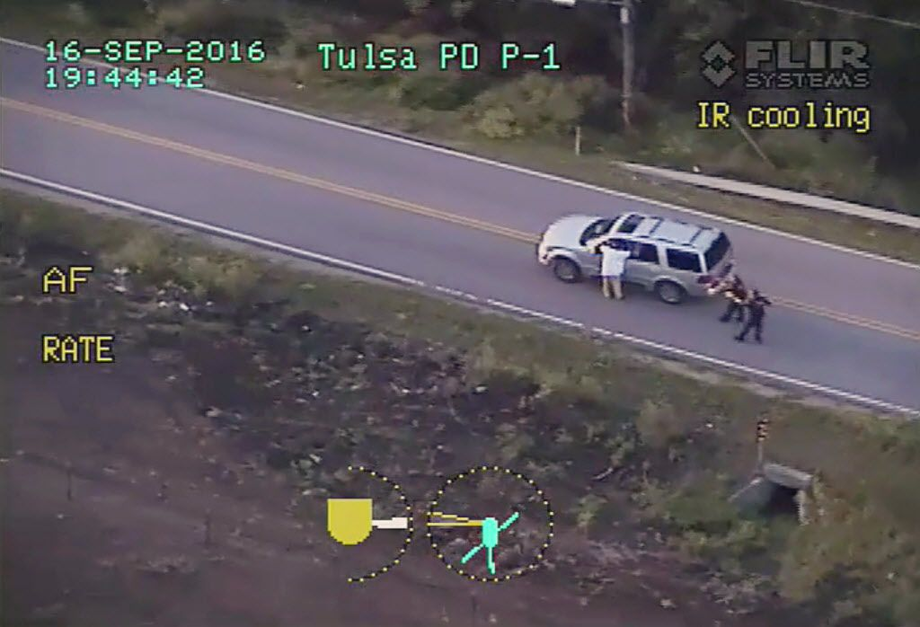 In this photo made from a Sept. 16 police video, Terence Crutcher (left), with his arms up, is pursued by police officers as he walks next to his stalled SUV moments before he was shot and killed by one of the officers in Tulsa.
